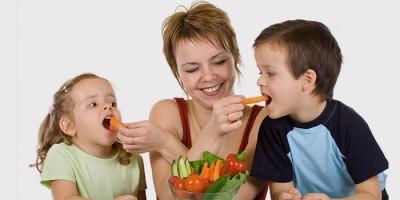 Мама кормит детей овощами для профилактики гнойной ангины