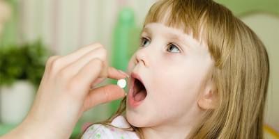 Мама дает ребенку таблетку от ангины