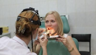 Врач-отоларинголог промывает девушке миндалины