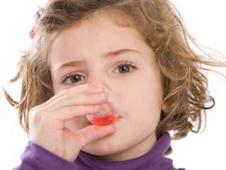 Девочка принимает микстуру от кашля