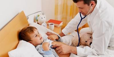 Доктор осматривает заболевшего ребенка