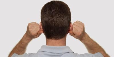 Мужчина делает массаж ушей, чтобы избавиться от заложенности